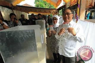 Calon Gubernur Jawa Barat periode 2013-2018 dari Partai Golkar, Irianto MS Syafiuddin atau Yance didampingi istrinya Anna Sophanah menunjukan surat suara saat melakukan pencoblosan Pilgub Jabar di TPS 02 Margadadi, Indramayu, Jawa Barat, Minggu (24/2). (ANTARA/Dedhez Anggara)