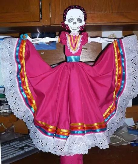 Calaveras con vestidos regionales de tela.