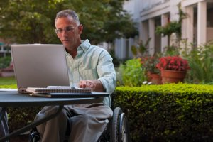 Chicago Social Security Disability Lawyer  Businessman with spinal cord injury working on a laptop