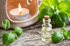 A bottle ofaromatera basil essential oil with fresh basil twigs and an aroma lamp