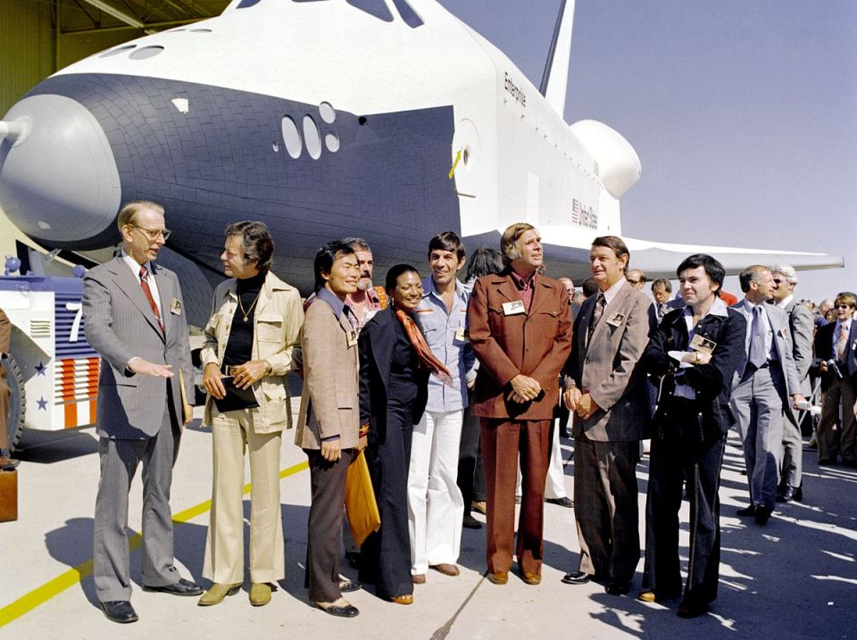 "Das NASA-Shuttle Enterprise vor der Werksanlage in Palmdale, mit der Star-Trek-Besetzung. Von links nach rechts: Dr. James C. Fletcher (damaliger Leiter der NASA), DeForest Kelley (Dr. ""Pille"" McCoy), George Takei (Mr. Sulu), James Doohan (Chefingenieur ""Scotty"" Scott), Nichelle Nichols (Lt. Uhura), Leonard Nimoy (Mr. Spock), Gene Roddenberry (der Erfinder von Star Trek), ein unbenannter Offizieller (vermutlich von der NASA) und Walter Koenig (Fähnrich Pavel Chekov)."