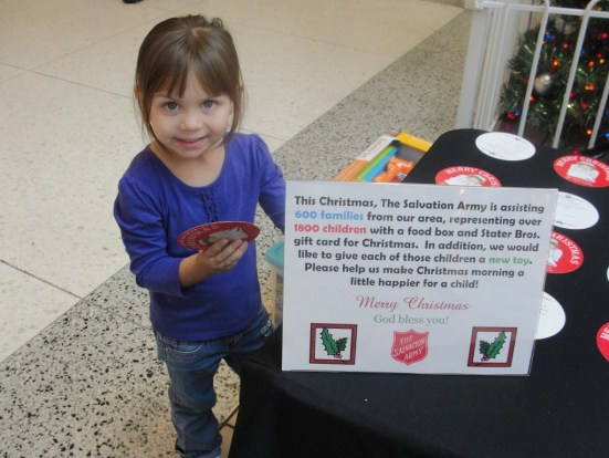 Three year old Allie Chavez is happy to give donations to The Salvation Army's Giving Tree Program. Photo by Paul Martinez.