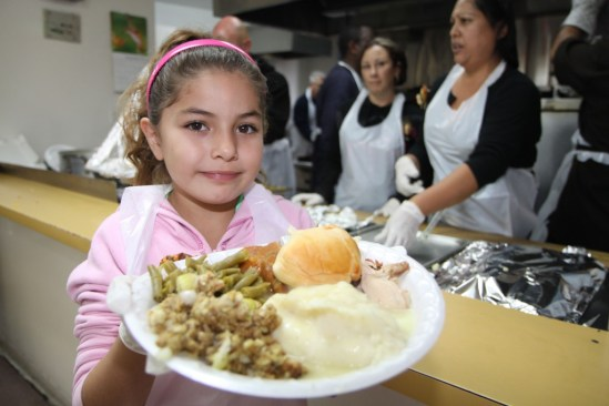 Proving that you are not too young to make a difference, Rae Ann Ortiz volunteers to serve holiday meals at the Salvation Army San Bernardino Corp. Photo by Ricardo Tomboc