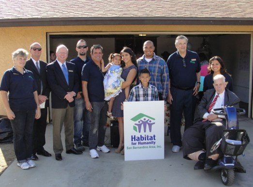 """The Espinoza family receives their new home.  Left to right:  Habitat for Humanity Barbara Keough, Secretary; Richard Brown; President; Dennis Baxter, Executive Director; John Biggs, ReStore manager; Tim Garcia, General Contractor; Aubrey Espinoza; Jessica Espinoza, Steven Espinoza, holding the Habitat for Humanity sign Steven Espinoza Jr.; Jack B. Russell, Vice President; Maritza Solis, Office Manager and Volunteer Coordinator; and Hesperia City Council Member Russell """"Russ"""" Blewett."""
