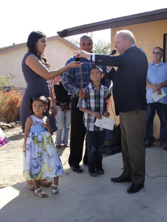 Getting the keys to their new home are left to right: two-year-old Aubrey, Jessica, six-year-old Steven Jr., and Steven Espinoza, from Habitat for Humanity Executive Director Dennis Baxter.