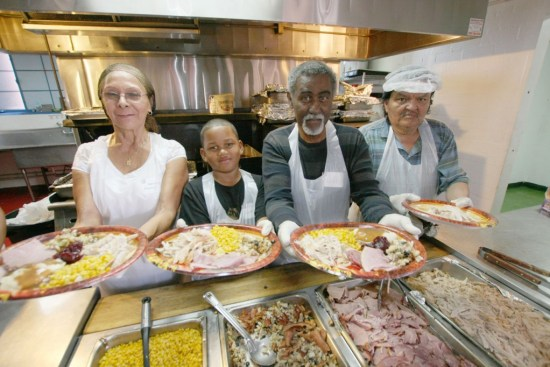 Volunteers serve Thanksgiving Dinner at  The Salvation Army: Serving on the food line (left to right) is Nancy Veaegas, Niyahn Summey, Walt Summey, and Robert Sanchez.  600 turkeys are needed for Christmas Dinners.