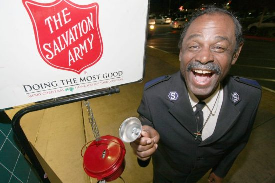 Photo 2 IMG_1652 Earl Perkins: Mr. Earl Perkins stands with his kettle by the entry doors at the Food 4 Less market on Victoria Ave. and Highland Ave. in San Bernardino. Earl is a Salvation Army Solider, and is in full uniform when he works. Earl has been with the Kansas City Salvation Army for over six years. Earl moved to San Bernardino four months ago, and is now a member of the San Bernardino Corps. Photo By Ricardo Tomboc