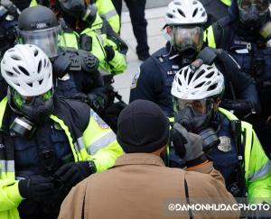 Angry citizen confronts a line of riot police.