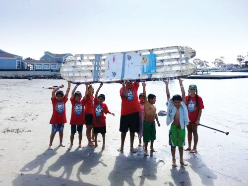 Members of the San Juan Capistrano-based Great Opportunities get ready to launch a stand-up paddleboard made entirely of recycled materials at Baby Beach. The group is working on its fourth such board for a member to race on in the 5th annual Mickey Munoz Mongoose Cup at the Dana Point Festival of Whales on March 8. Courtesy photo