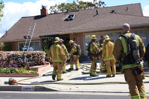 Orange County Fire Authority firefighters clean up and monitor a home following a fire at a home in the 32000 block of Bluffside Drive in Dana Point Tuesday. Photo by Andrea Swayne