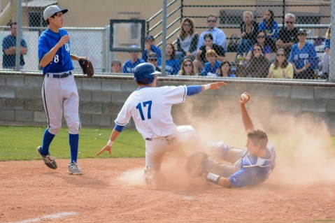 Dana Hills catcher David Clawson, right, holds on for the tag-out of El Toro's Brandon Helmick in the second inning on May 13. Photo: KDahlgren Photography