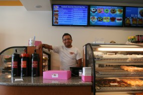Employee Adrian Guzman is ready to help Dana Point customers choose from Donut Star's large variety of freshly-made donuts and pastries. Photo: Jacob Onofrio