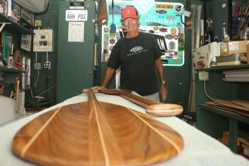 "Jean Pierre ""The Fly"" Van Swae stands next to an outrigger canoe paddle he built recently in his shop in Dana Point. He has been making surfboards, paddles and other sea-faring devices for more than 55 years. Photo: Eric Heinz"