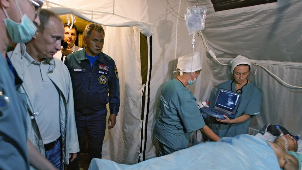 Vladimir Putin (2nd L) looks at a man injured during fighting in South Ossetia during a visit to a field hospital in Vladikavkaz, the provincial capital of the region of North Ossetia