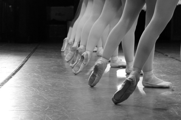 A long line of legs wearing ballet shoes. A picture of a ballet class.