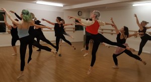 A group of young women in a ballet studio doing an dancing pose.