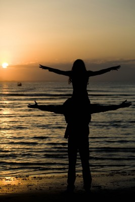 Photo: Man with child on shoulders, both have arms outstretched facing a sunrise.
