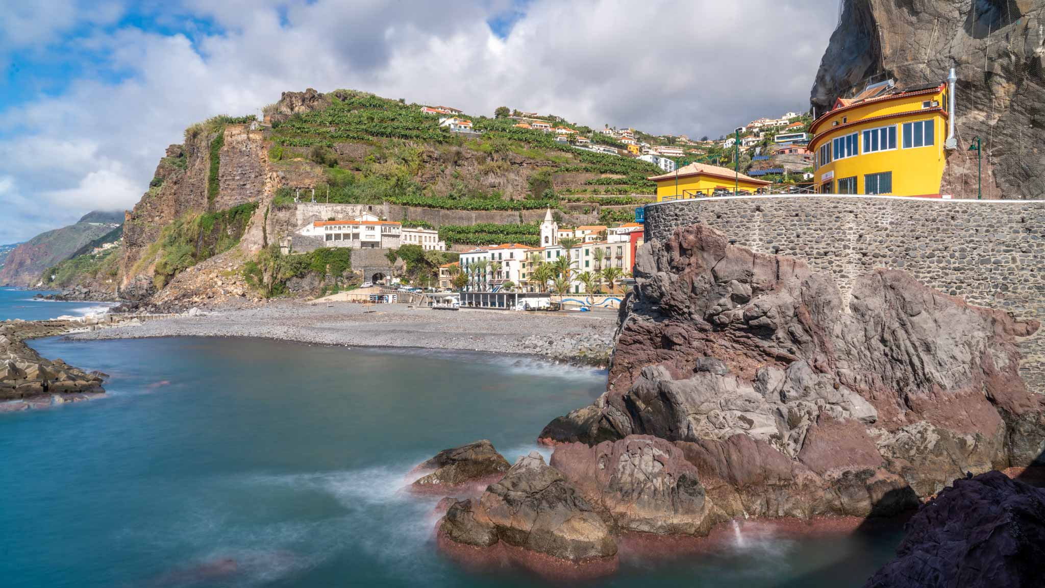 The village of Ponto do Sol in Madeira, with green hills and a small bay for swimming