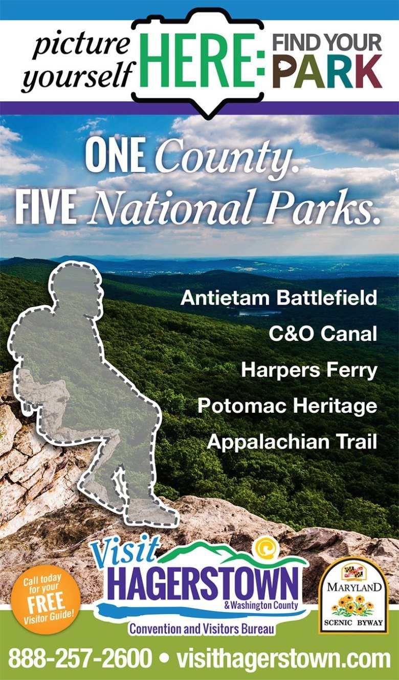 A photo taken from High Rock in Maryland, showing a landscape of lush green hills as far as the eye can see. The outline of a hiker is resting on a rock formation in the foreground of the photo. The image is advertising the five national parks that Washington County, MD contains.