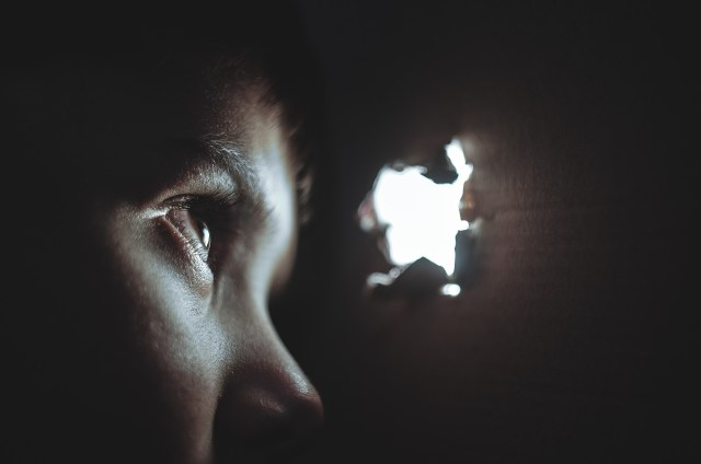 scared child hiding in dark