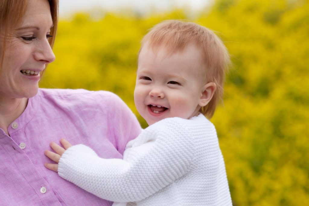 Spring Mini Session - Mother Holding Smiling Baby - yellow blossoms in back - www.daniellebustamante.com - #springmini #nhspringminisession