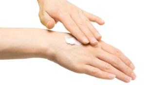 Mão esquerda passando creme na mão direita, entre os dedos e o punho