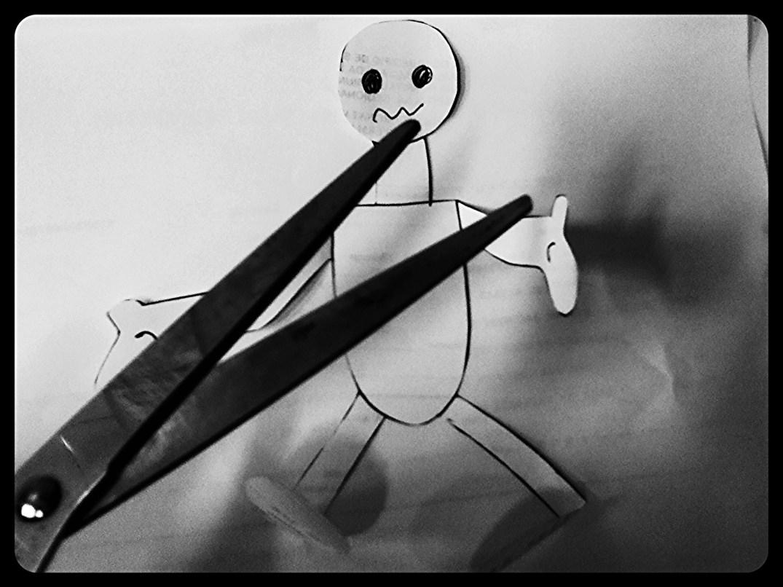 um boneco de papel sendo cortado por uma tesoura