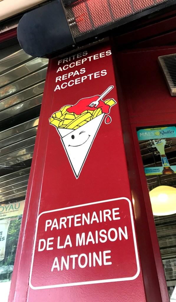 Dette skilt giver dig adgang til at købe drikkevarer og spise dine fritter fra Maison Antoine