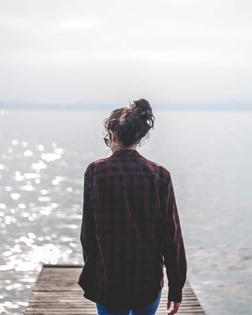 woman wearing black and red gingham walking on wooden dock