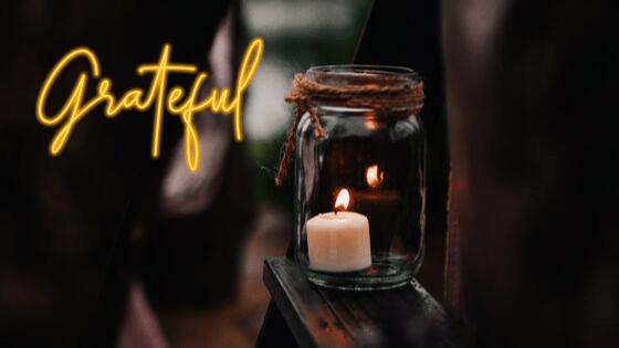 Płonąca świeczka w słoiku postawionym na desce. Z lewego boku napis: Grateful - wdzięczność