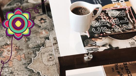 stoli, a na nim kubek z kawą i gazeta