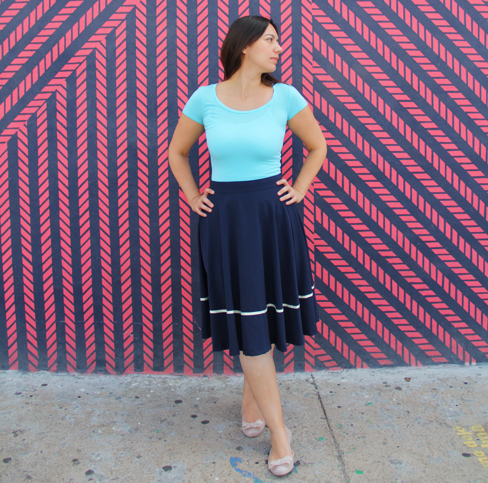 Coco wearing an aqua jersey top with a navy midi skirt.
