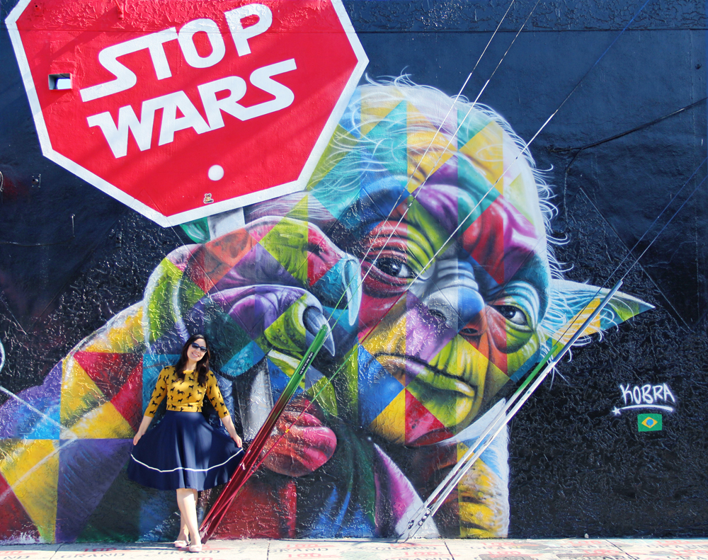 Yoda Stop Wars Mural in Wynwood Miami. Horse all over pattern sweater in mustard with navy midi skirt and nude flats