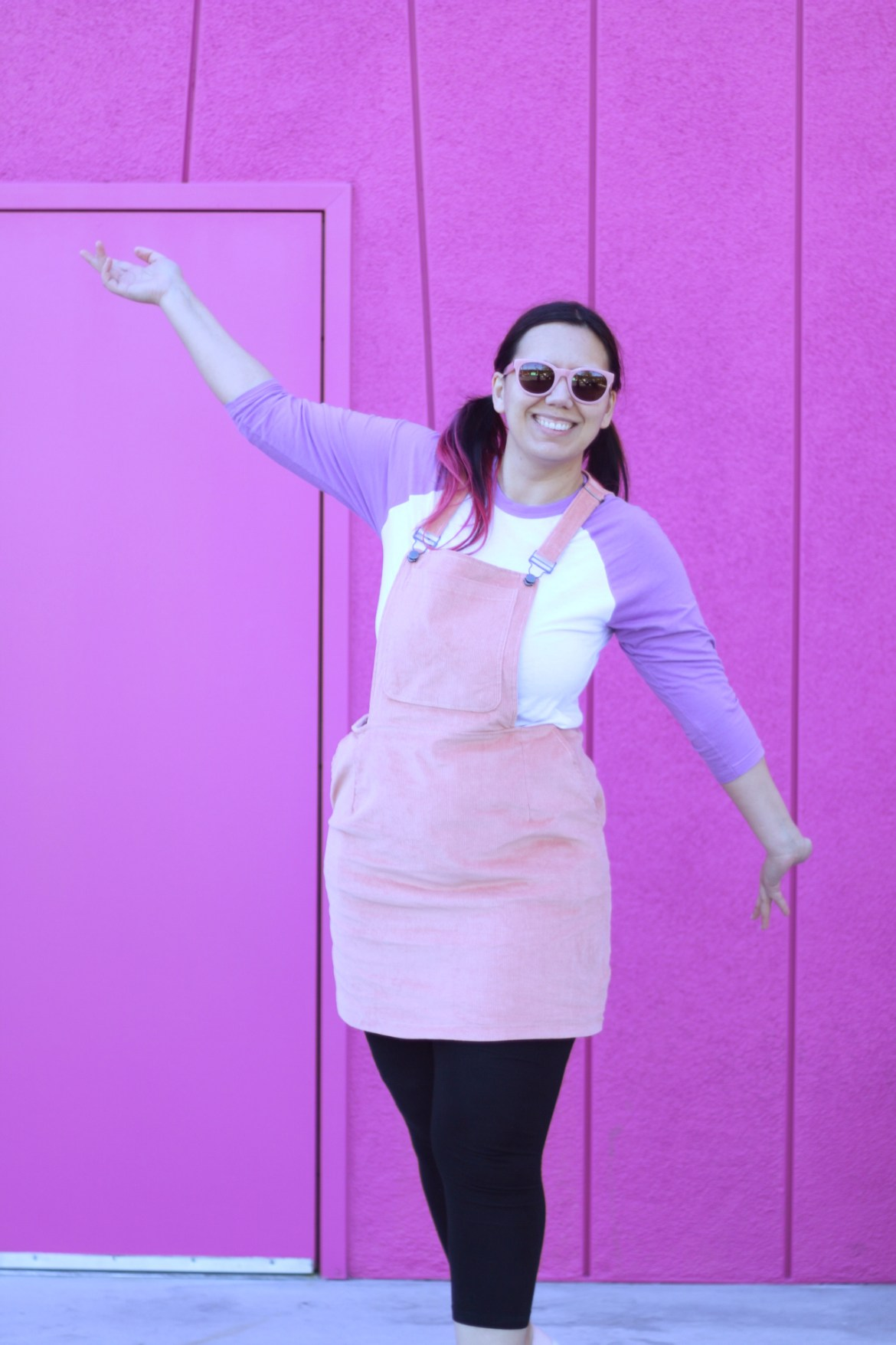 Care Bear inspired comfortable travel outfit with a pink pinafore and a lilac raglan shirt