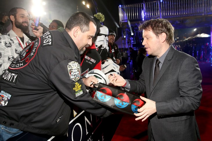 "HOLLYWOOD, CA - DECEMBER 10: Director Gareth Edwards signs an autograph for a fan at The World Premiere of Lucasfilm's highly anticipated, first-ever, standalone Star Wars adventure, ""Rogue One: A Star Wars Story"" at the Pantages Theatre on December 10, 2016 in Hollywood, California. (Photo by Jesse Grant/Getty Images for Disney) *** Local Caption *** Gareth Edwards"