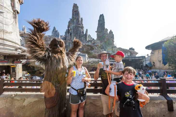 Eight-year-old Jonathan Ridgeway of Ocean Springs, Mississippi (front right) becomes the 1 millionth guest to take to take the controls of Millennium Falcon: Smugglers Run at Star Wars: Galaxy's Edge at Disneyland Resort in Anaheim, Calif., Tuesday, July 16, 2019. Left to right: Chewbacca joins Becky Ridgeway, her husband, Roger Ridgeway, son Logan, 4, and Jonathan, 4, as they toast Blue and Green Milk in Star Wars: Galaxy's Edge after riding Millennium Falcon: Smugglers Run. This significant milestone comes just weeks since the land opened. (Joshua Sudock/Disneyland Resort)