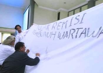 Pengumpulkan tanda tangan di selembar kain putih simbol penolakan remisi untuk Nyoman Susrama, pembunuh jurnalis Radar Bali, AA Gde Bagus Narendra Prabangsa. Jurnalis berharap pemerintah tak sepelekan kekerasan terhadap jurnalis. Foto: Dara.co.id