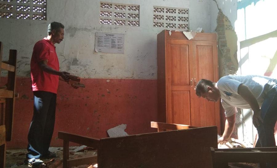 Masyarakat Desa Cijolang membersihkan sisa atap yang ambruk di ruang kelas SDN Cijolang 2, Kecamatan Limbangan, Kamis (24/10/2019). Foto: dara.co.id/Beni