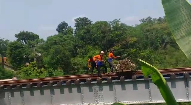 Tiga petugas kebersihan dari PT KAI membuang sampah ke sungai Cisokan (Foto: Istimewa)