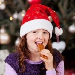 Little girl wearing a colourful red Santa hat eating Christmas candy as she looks at the camera with a smile