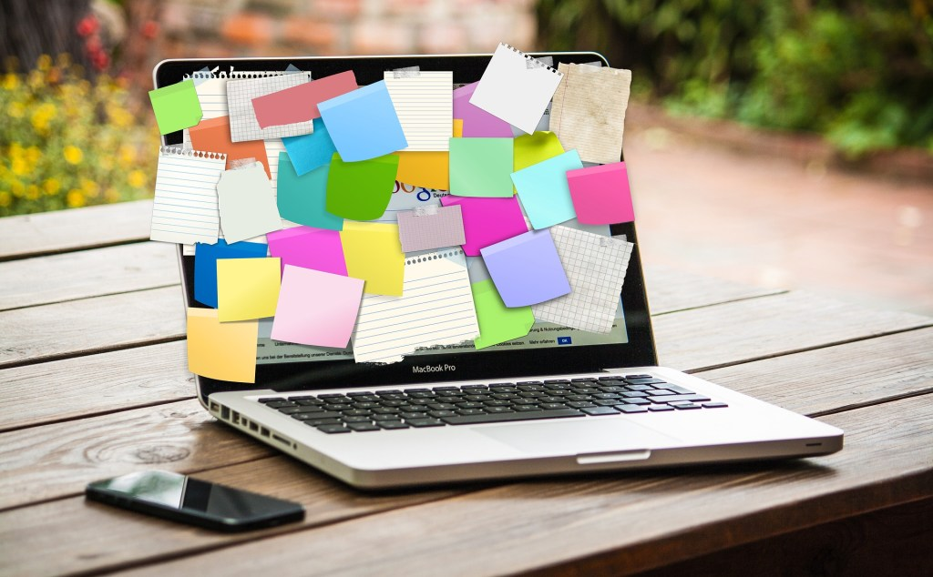 A laptop with sticky notes pasted across almost the entire screen depicting our brains when multitasking