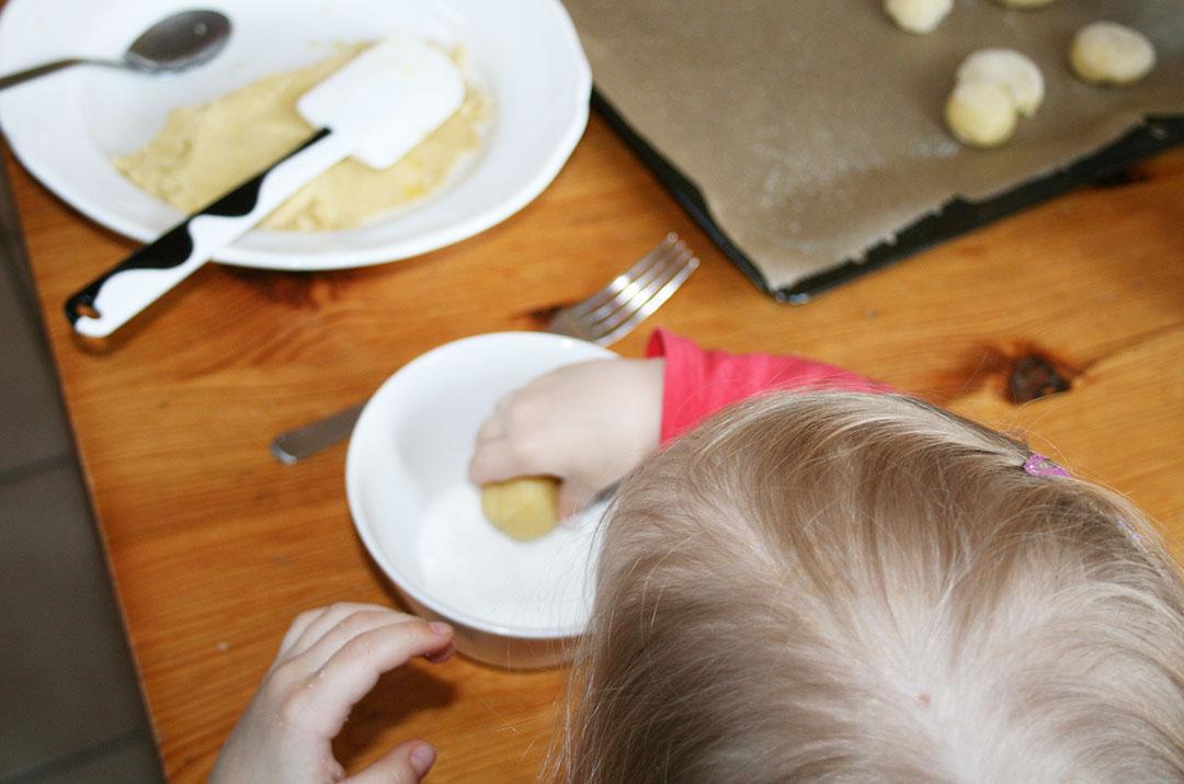 Foto von meiner Tochter, wie sie die Kugel aus Butterteig in den Zucker drückt . Darjas Welt