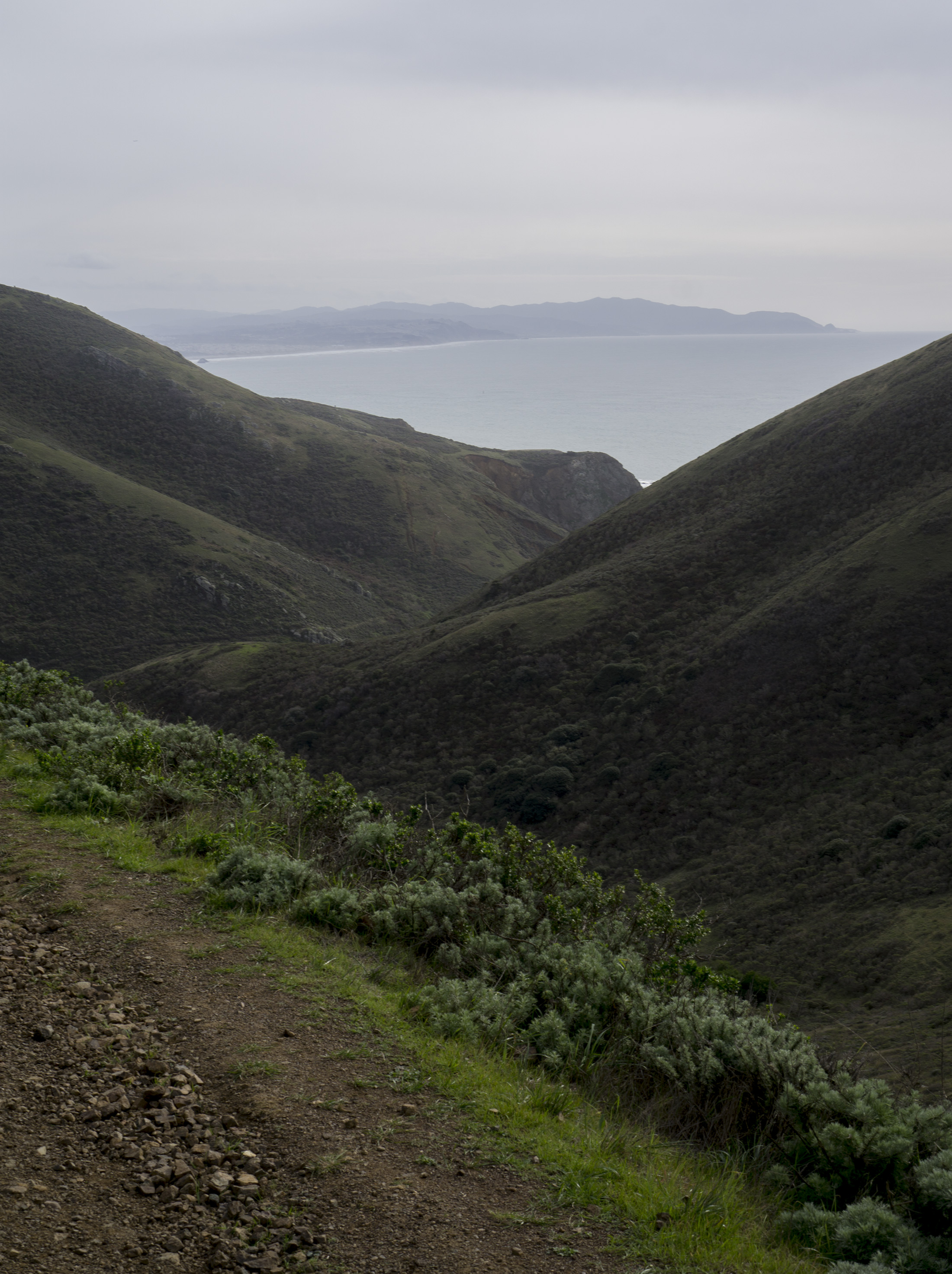 Pacific Ocean peeking through mountains along Tennessee Valley Trail, Marin Headlands, Golden Gate National Recreation Area / Darker than Green