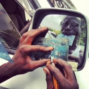 A man engraving a side mirror on a newly imported car. Photo: Daniel Hayduk