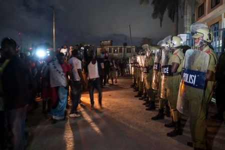 Police stand guard outside the tallying station in Kinondoni as opposition supporters celebrate throughout the night. Photo: Daniel Hayduk