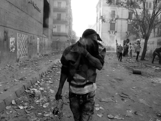 CAIRO.EGYPT.22/11/2011. A man tries to protect themselves from tear gas with the bow jacket in Mohamed Mahmoud st. Protesters during clashes with the Egyptian riot police near Tahrir square in Cairo. Egypt's civilian Cabinet has offered to resign after three days of violent clashes in many cities between demonstrators and security forces, but the action failed to satisfy protesters deeply frustrated with the new military rulers.(GABRIELE MICALIZZI/FOR NYTIMES MAGAZINE)