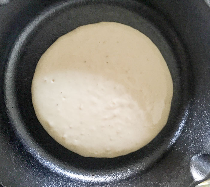 cooking pancake in cast iron skillet