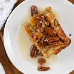 piece of bread pudding topped with pecan halves and vanilla glaze