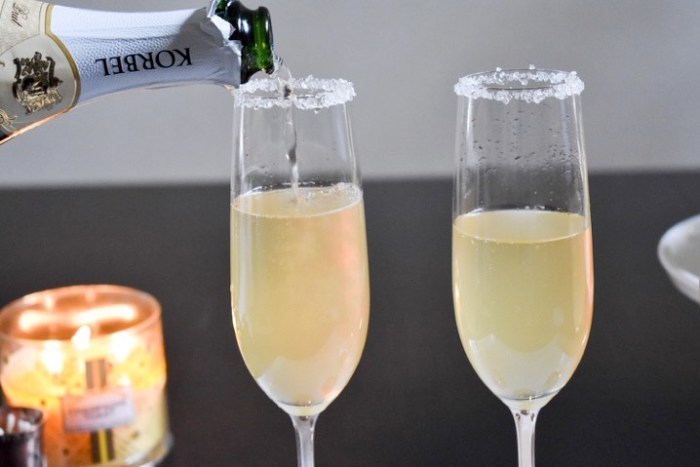 pouring champagne into sugar-rimmed flutes