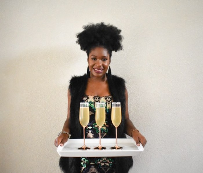 Dash of Jazz holding tray of citrus champagne sparkler cocktails